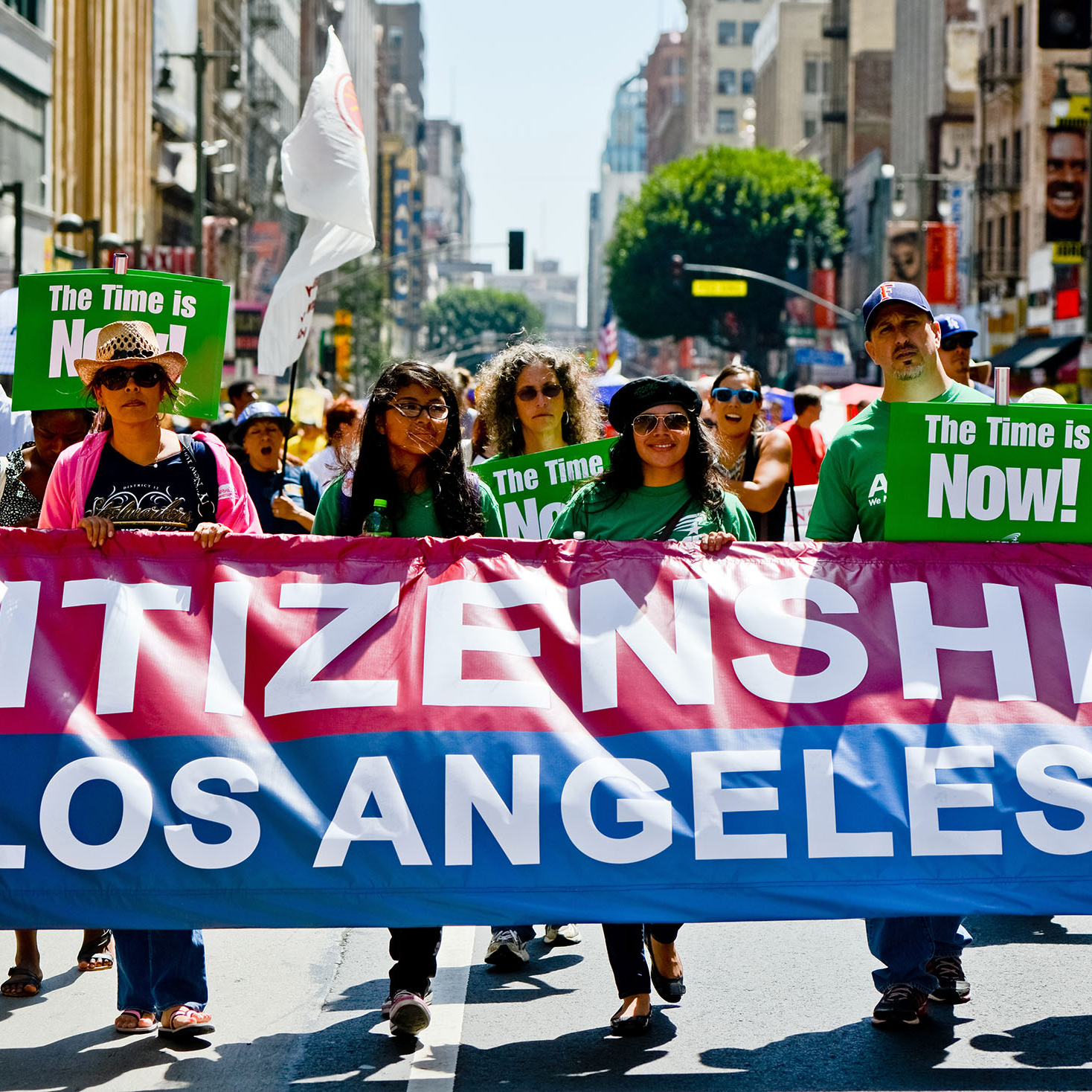 Los Angeles, USA - May 1, 2013: May Day March in Los Angeles Downtown, USA. People holding banners representing different social structures, organizations. March was mostly dedicated to Immigration reform discussed. Posters in English and Spanish. This group of people carrying banner saying: Citizenship now. Los Angeles Unions.